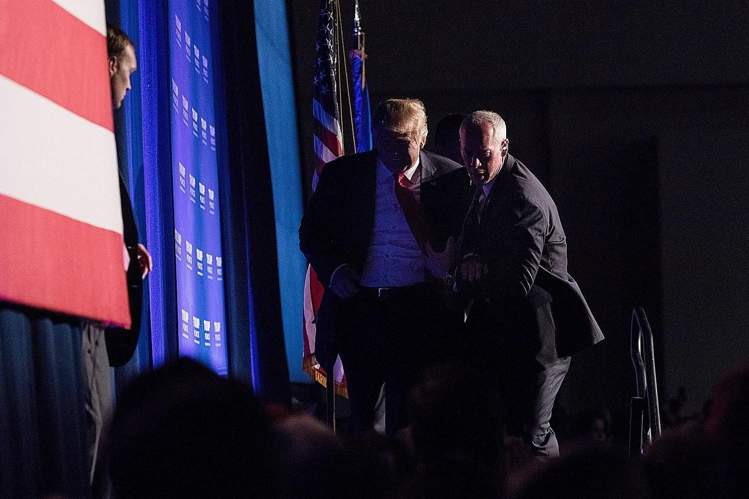 """Mr Trump being rushed off the stage by Secret Service agents after someone in the crowd yelled """"gun"""" at his rally in Reno, Nevada, on Saturday. No weapon was found on the man thought to be a threat to him, and the Republican candidate returned minute"""
