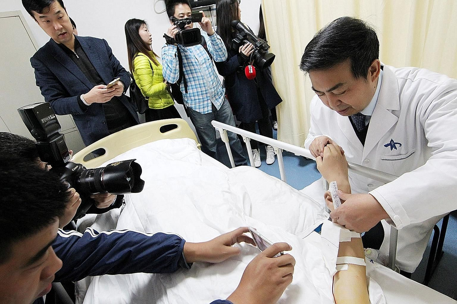 """Reporters (left) snapping photos of the """"ear"""" (below) growing on the arm of a man in China who lost his right ear in an accident."""