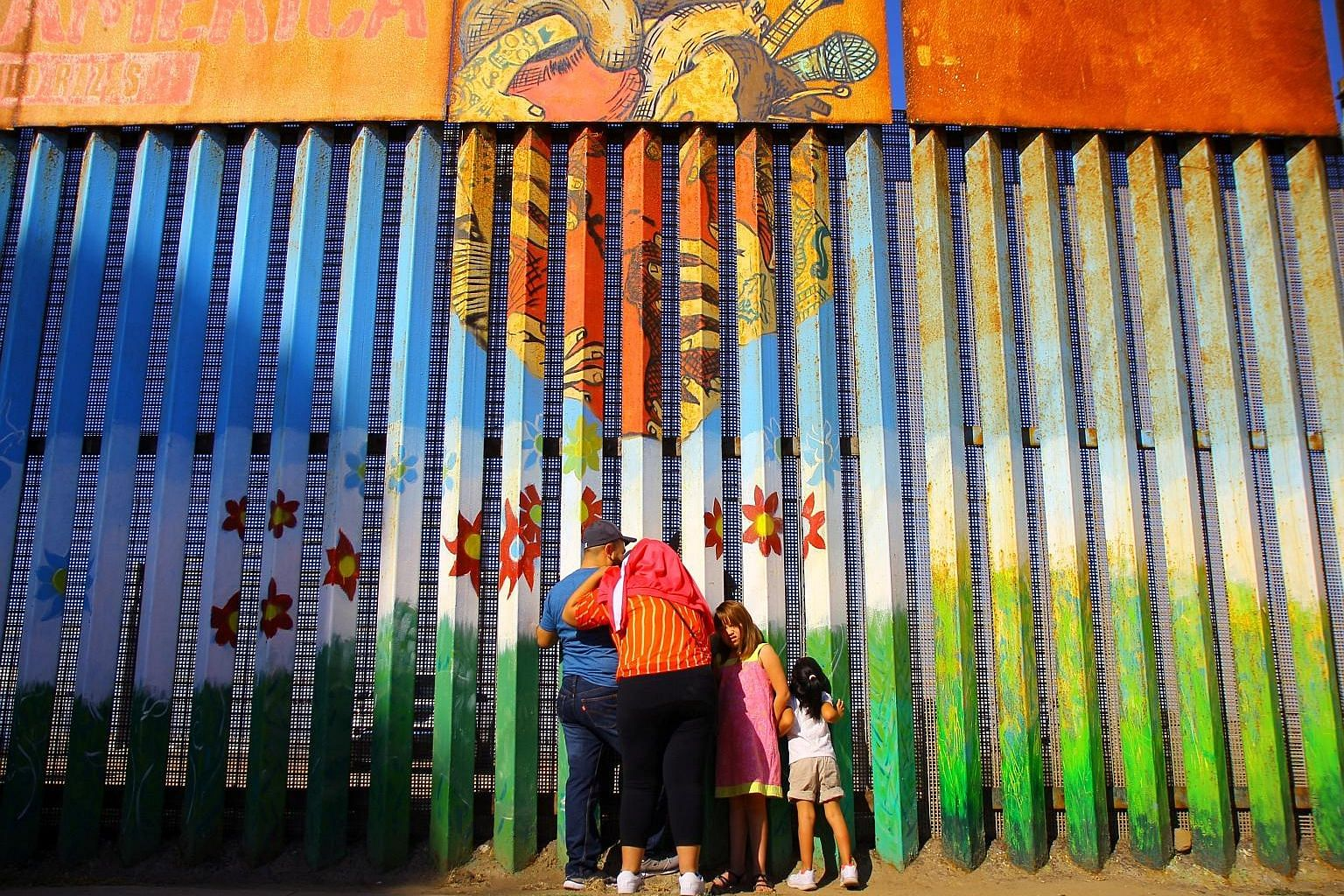 People in Tijuana, Mexico, speaking to relatives across the border in the US on Sunday. Mr Trump will have to ask Congress for the budget to build a wall - a tall order, say political analysts.