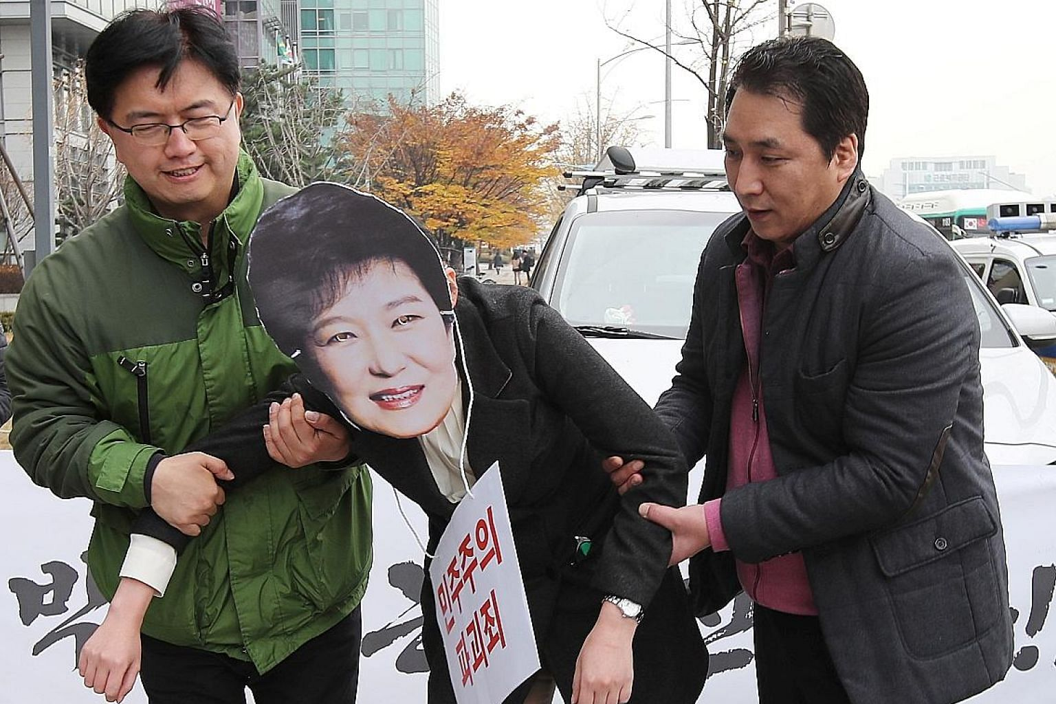 Demonstrators, one of whom is wearing a mask of President Park, taking part in a rally calling for the leader to step down. The snowballing saga is giving both the President and nation a bad name.