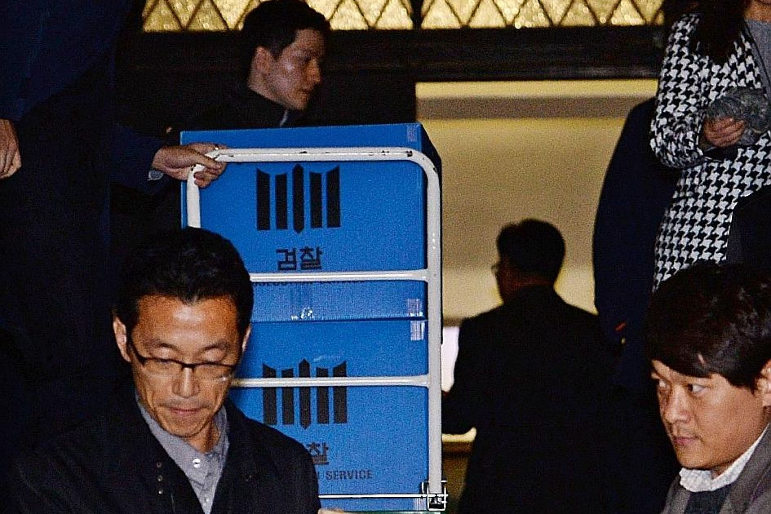 Prosecution investigators confiscating items from Ewha Womans University in Seoul yesterday during a raid amid allegations that the university gave unlawful favours to Choi's daughter.