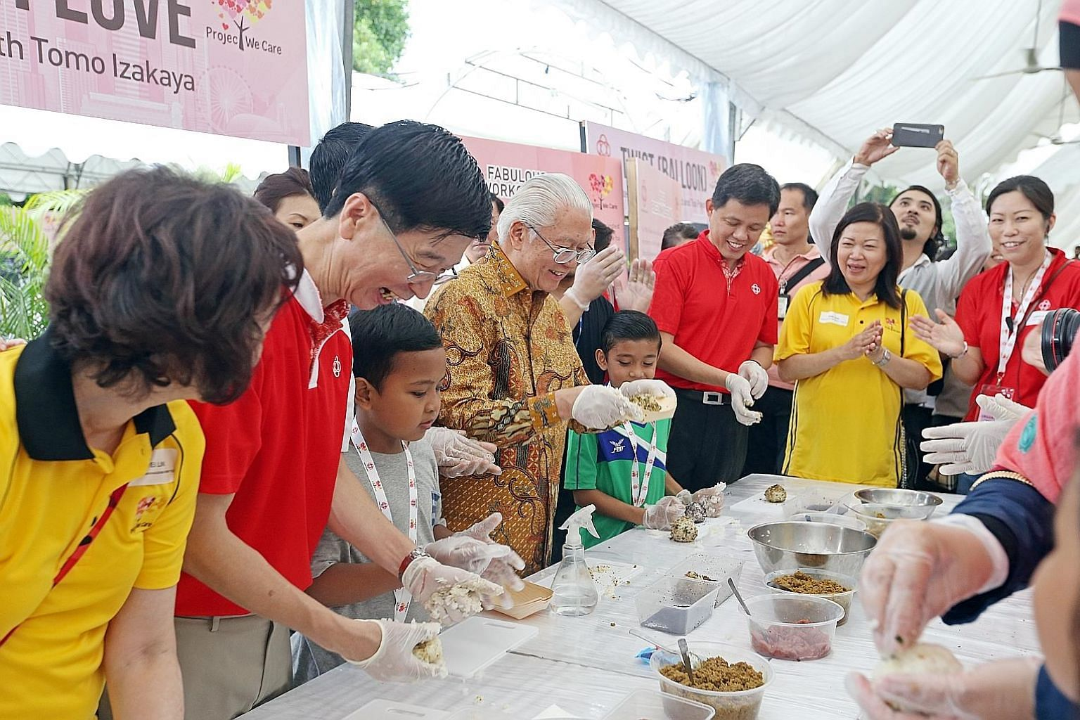 President Tony Tan Keng Yam making rice balls for beneficiaries of the new Project We Care Enrich at the Istana yesterday. With him were People's Association (PA) chief executive director Ang Hak Seng (second from left); Minister in the Prime Ministe