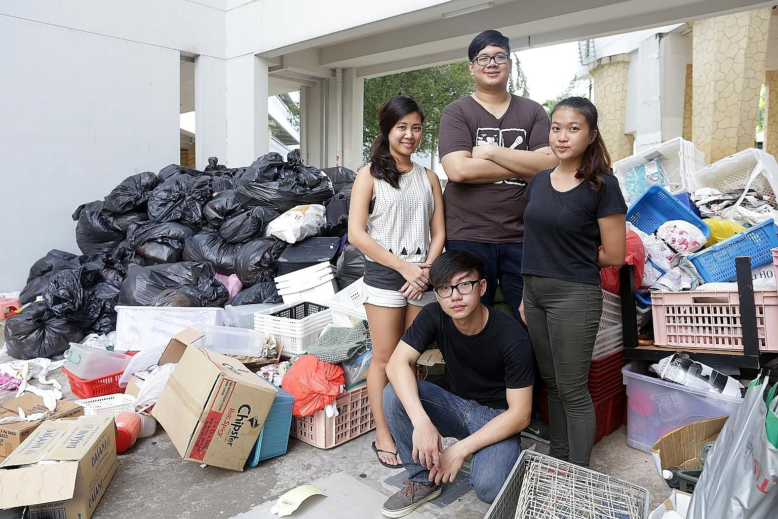Clockwise from right: Core team members of Silver Ribbon's youth chapter Trini Low, 21, and Jonathan Kuek, 26, with volunteers Keren Lee, 25, and Gerald Tan, 21. Around them is a portion of the clutter that 25 young volunteers removed from the flat o