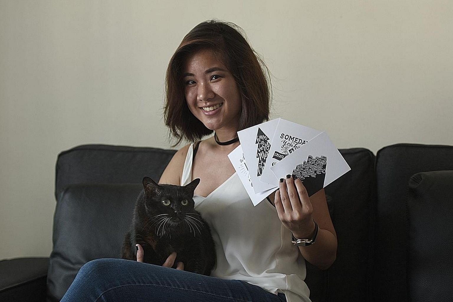 Ms Chew with one of the two cats her family adopted. The 24-year-old hand-letterist, who is selling hand-drawn cards to raise money for Oasis Second Chance Animal Shelter, hopes to raise $500 by this month.