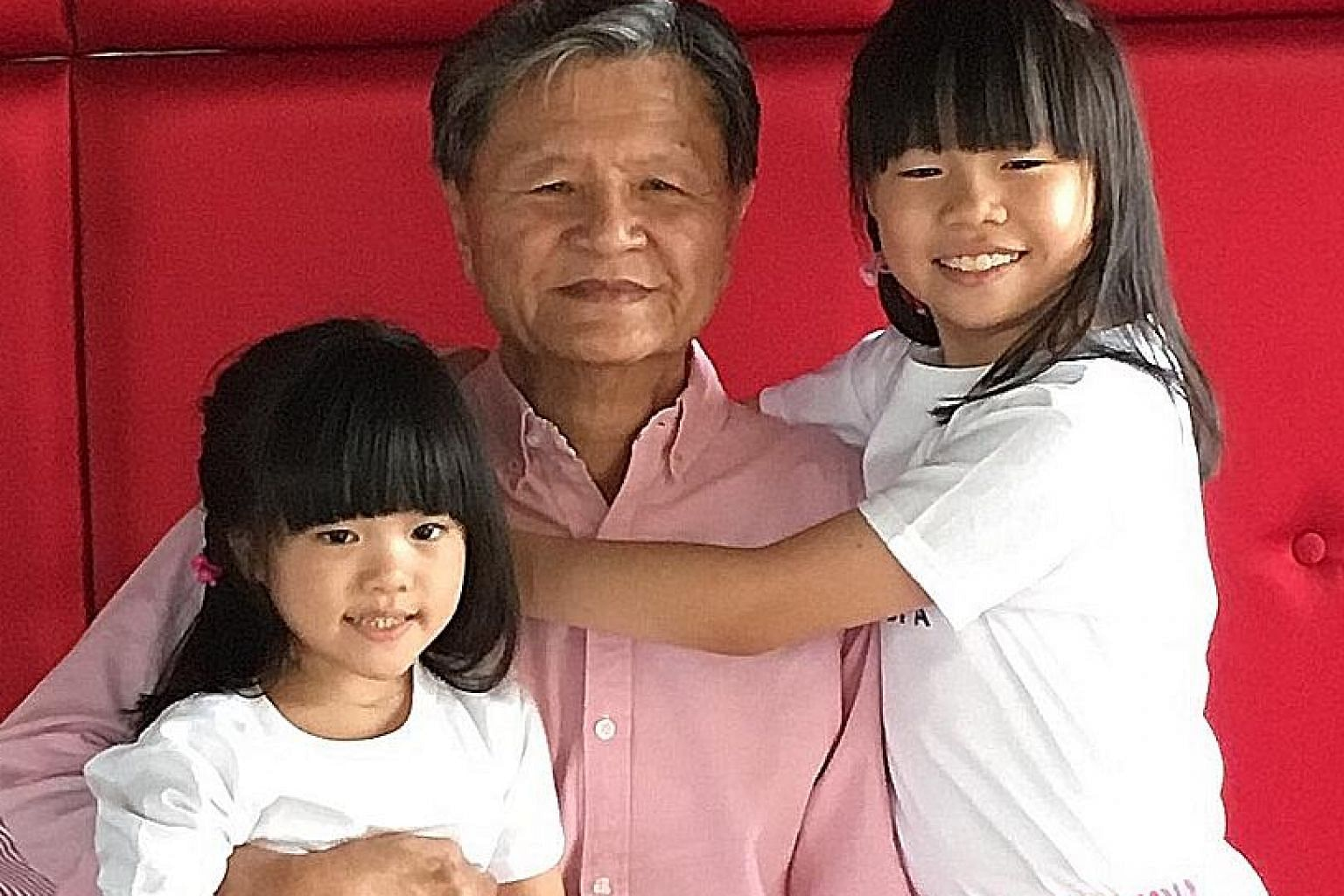 Mr Neo with his granddaughters Sheer Ann, five, and Sheer Zee, nine. He is passionate about giving people a helping hand when he can and displaying graciousness.