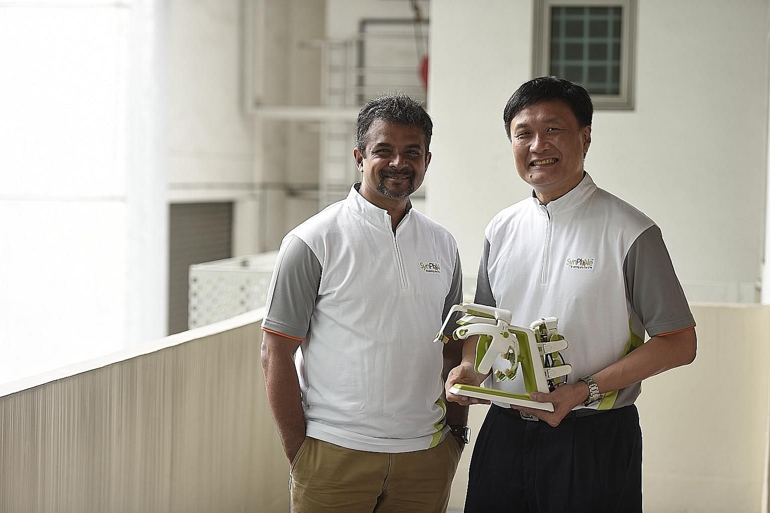 "Dr Banerji and Dr Heng with the SynPhNe device, which stands for ""synergy between physio and neuro"". The specially designed headset comes with neural sensors and an arm glove with muscle activity sensors."