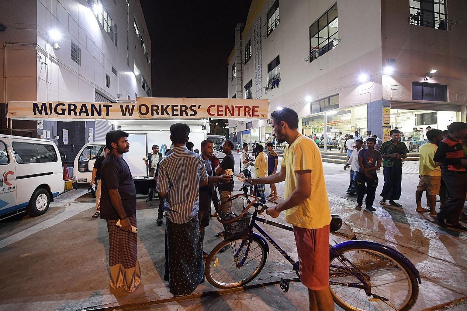 Mr Raja Ramasamy Raj (third from left), 39, and Mr Jeyabal Simeon (left), 32, both volunteers with the Migrant Workers' Centre, talking to migrant workers in Tuas View Square. The centre has conducted outreach to more than 650,000 foreign workers sin