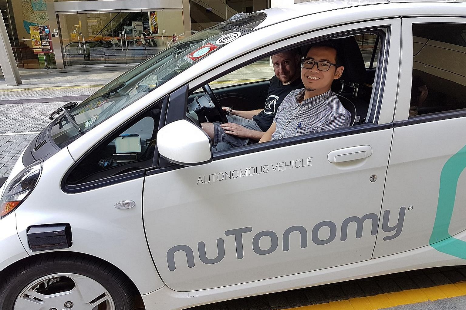 The reporter with nuTonomy safety engineer Greg Butron in the start-up's self-driving Mitsubishi i-MiEV.