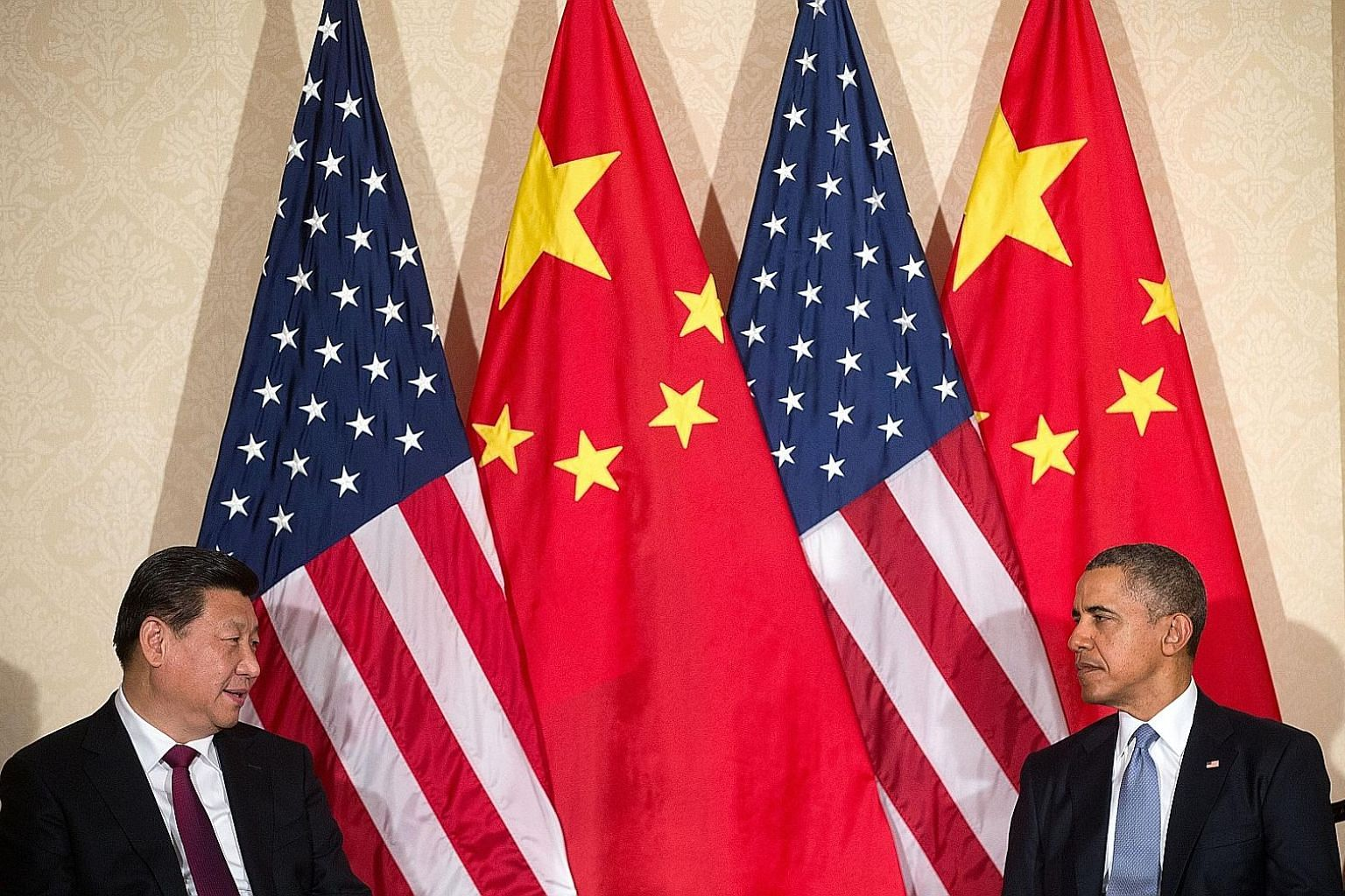 Mr Xi and Mr Obama at a meeting in the Netherlands in 2014. As America's influence declines, the steel-willed Chinese leader has risen above a shaky economy and the embarrassment of being all but declared an outlaw in the South China Sea to impose hi
