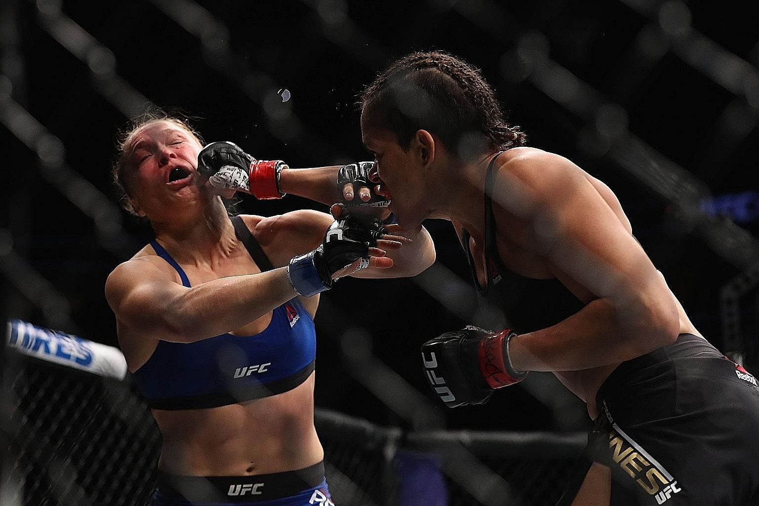 Brazilian Amanda Nunes delivering a punch on Ronda Rousey during their bantamweight championship bout. Having taken a 13-month break from fighting competitively, the American's comeback ended in defeat.