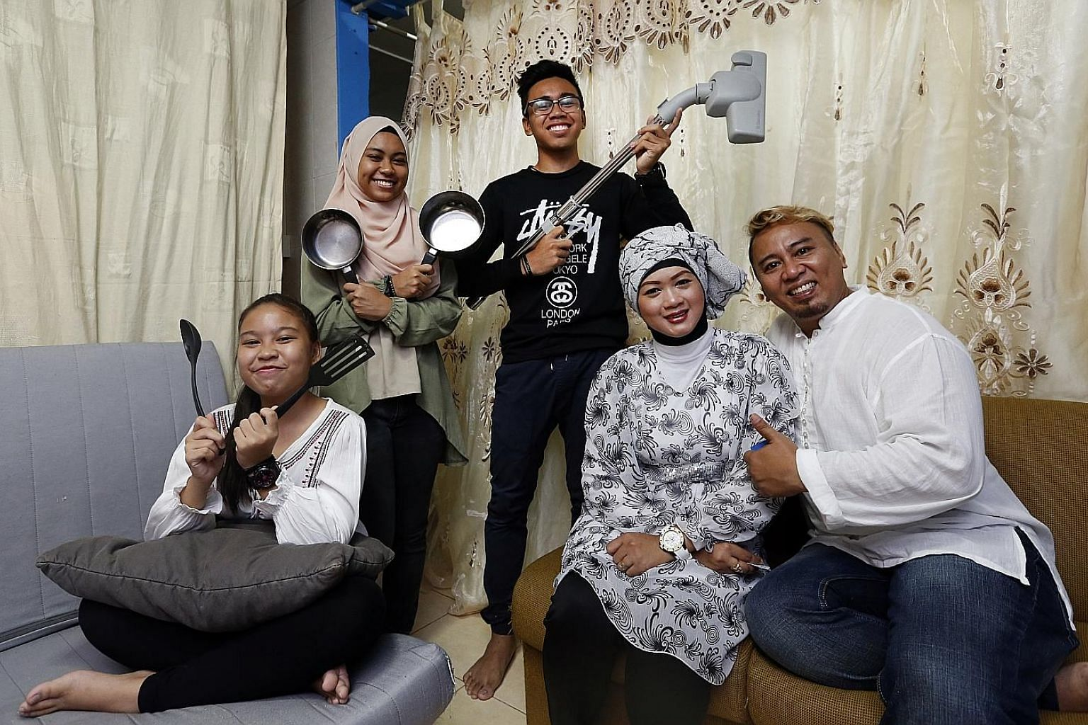 Mr Erwan Agos and his wife, Ms Cici Rahayu, get help around the house from children (from left) Mellisha, Melwani and Ermanto.