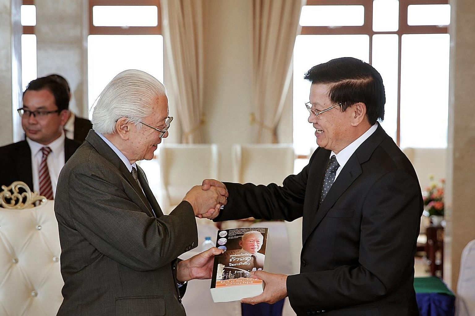 Dr Tan presenting a Lao edition of the book, From Third World To First: The Singapore Story From 1965 To 2000, which was written by founding prime minister Lee Kuan Yew, to Mr Thongloun.