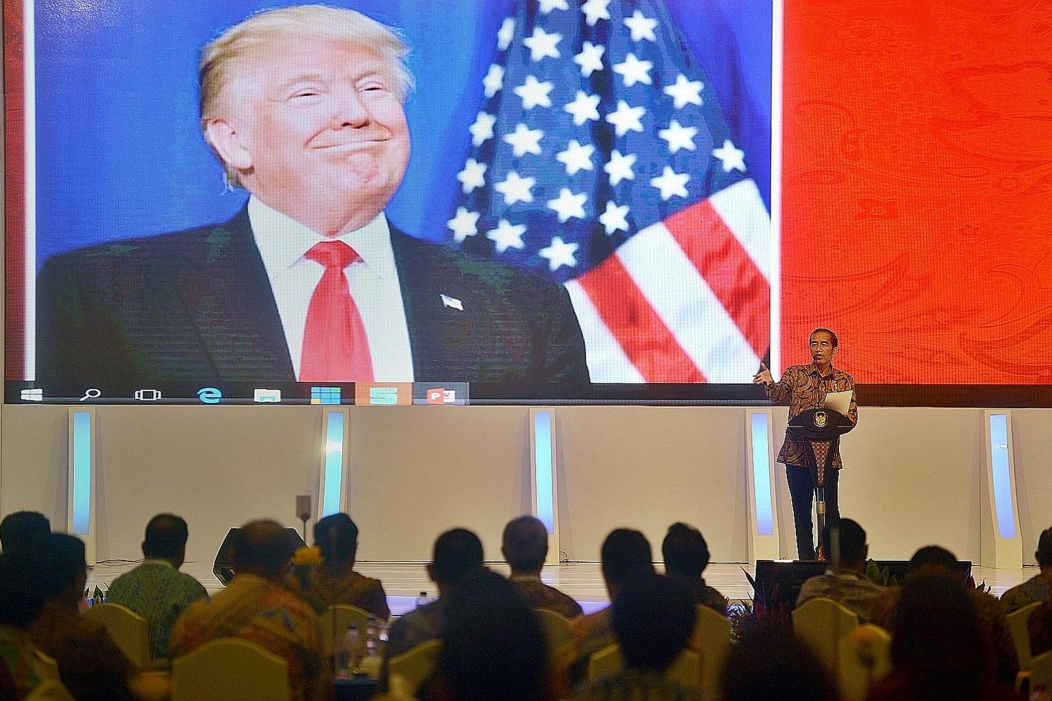 Indonesian President Joko speaking to local company executives as a picture of Mr Trump is shown on the screen behind him at the Kompas CEO forum in Jakarta last November. According to the writer, Mr Joko, like the incoming US president, is a product
