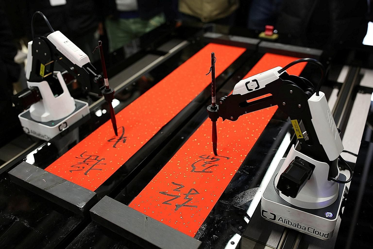 "Robots writing calligraphy couplets for employees at Alibaba's headquarters in Hangzhou, China, on Monday, ahead of the Chinese New Year. Employees were invited to ""wake up"" AliCloud artificial intelligence ET, talk to it and then get tailored Chines"