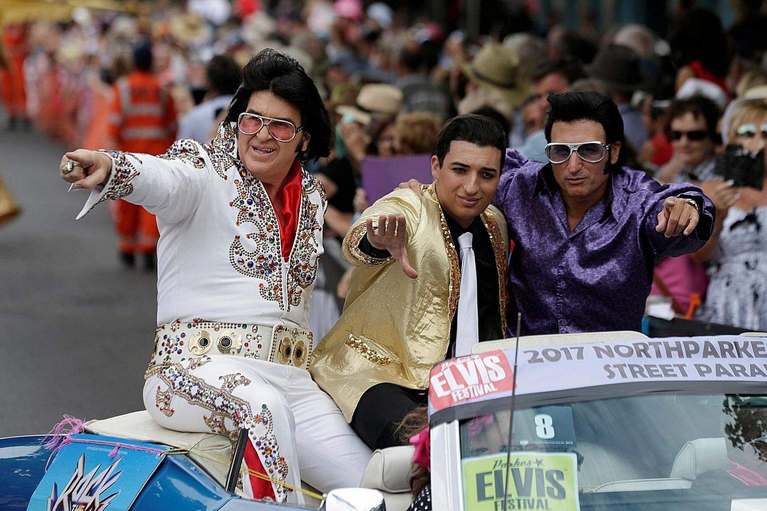 Men dressed as Elvis Presley ride in the back of a convertible during a street parade at the annual Parkes Elvis Festival last Saturday. Across the country, small towns have been finding creative ways to put themselves on the tourist map.