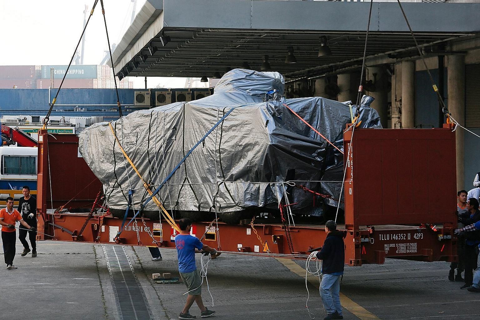 One of the nine Singapore Armed Forces Terrex armoured vehicles being prepared to be loaded onto a truck at a cargo terminal in Hong Kong yesterday afternoon. On Tuesday, more than two months after the vehicles were detained while in transit on the w
