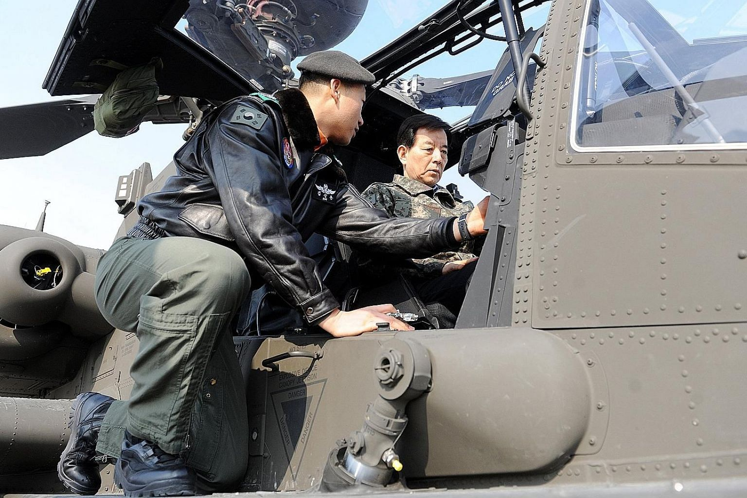 Above: South Korean Defence Minister Han Min Koo (right) inspecting an Apache helicopter during a visit to the Air Operations Command in South Korea on Monday. Left: A soldier training on the launch pad of a Patriot PAC-3 advanced missile, at a unit