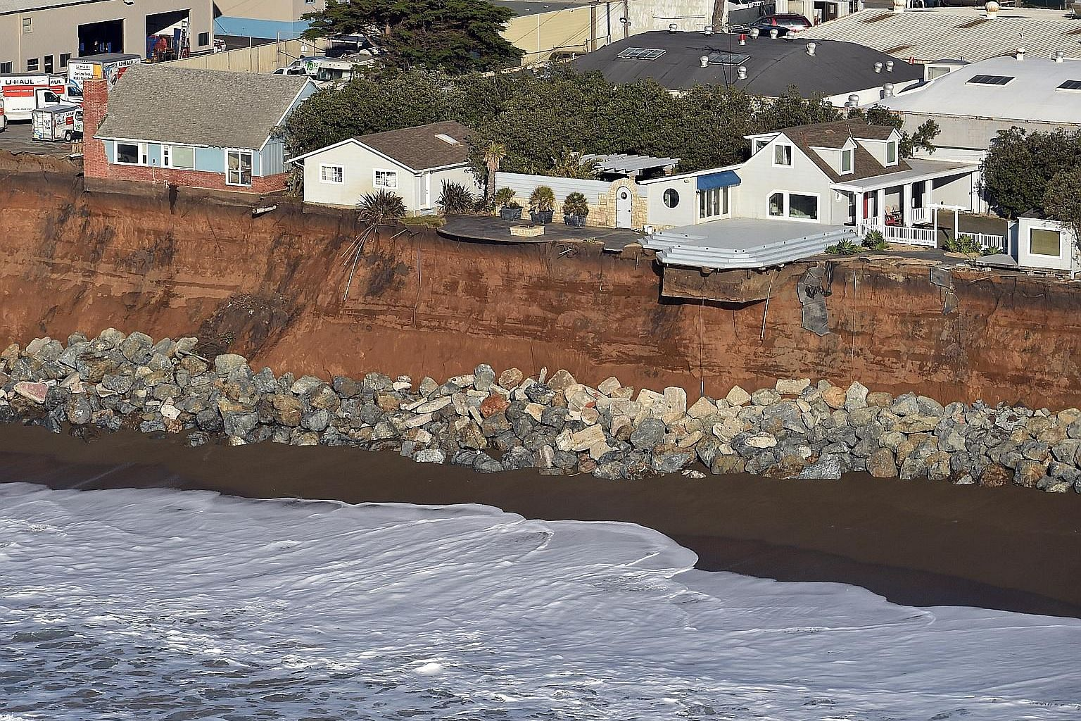Houses resting on the edge of an eroding cliff in Pacifica, California, in January last year. Storms and powerful waves caused by last year's unusually potent El Nino have intensified erosion along nearby coastal bluffs and beaches in the area, as we
