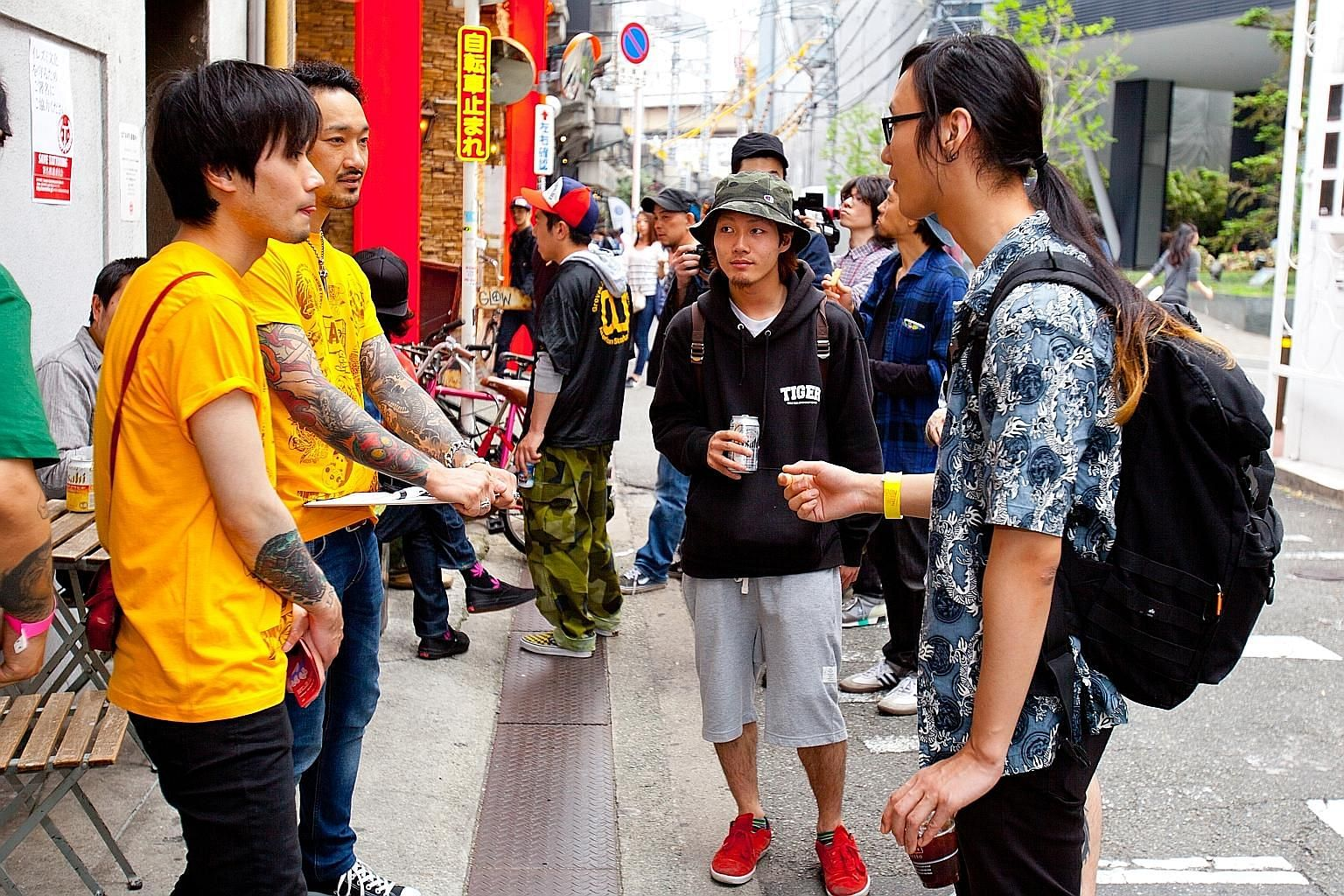 Mr Masuda (far left, foreground), who started the Save Tattooing in Japan campaign, speaking to people during an event in Osaka to raise awareness about the craft, and (left) tattooing a client. The tattoo artist's business has been suspended for ove
