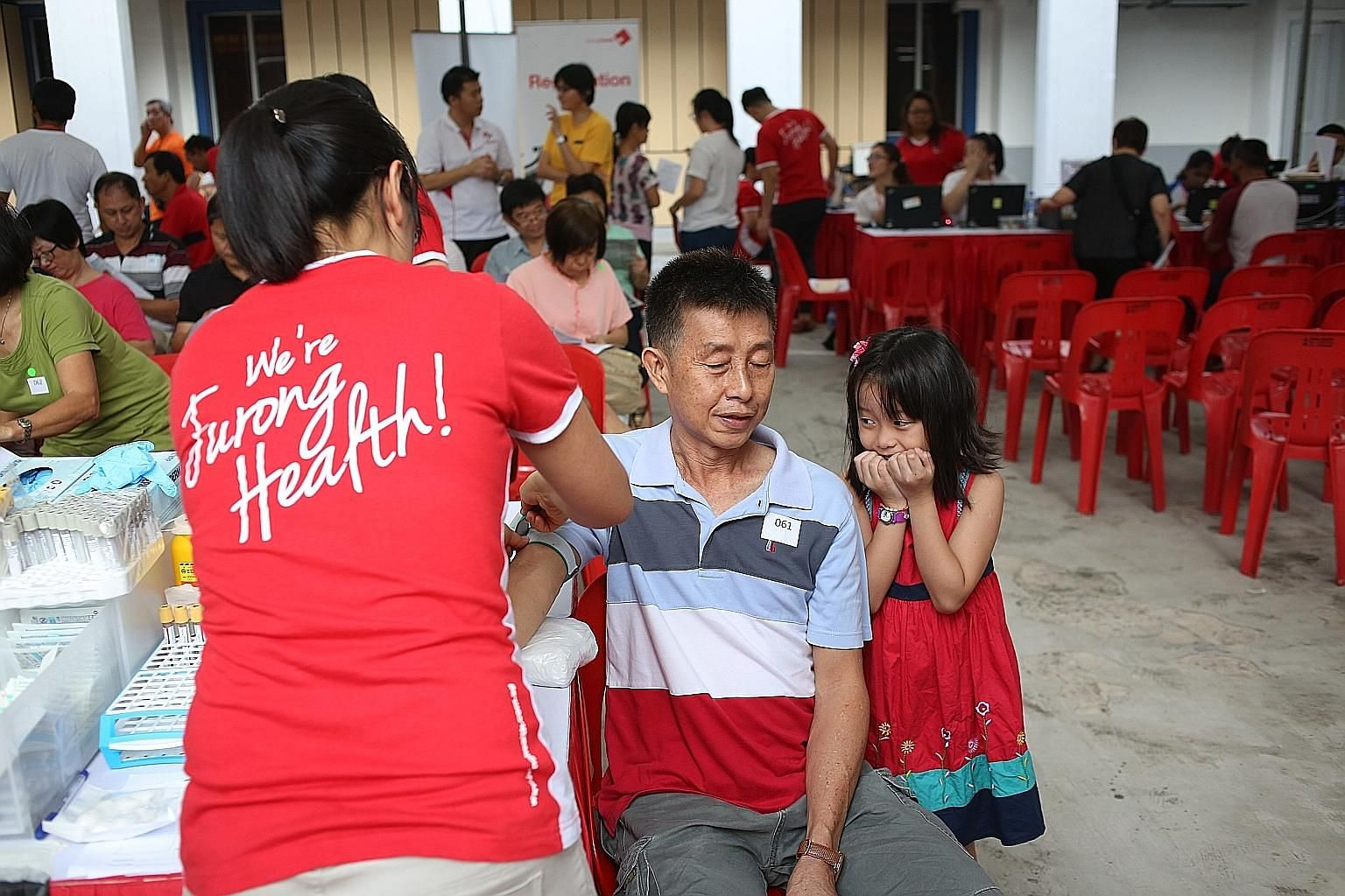 Chia Yi Leng, eight, trying to put on a brave front while her father, Mr Chia Kwong Weng, 56, prepared to have his blood drawn for a test yesterday. He was among those given free health screenings under a new One and Health Programme that saw some 30