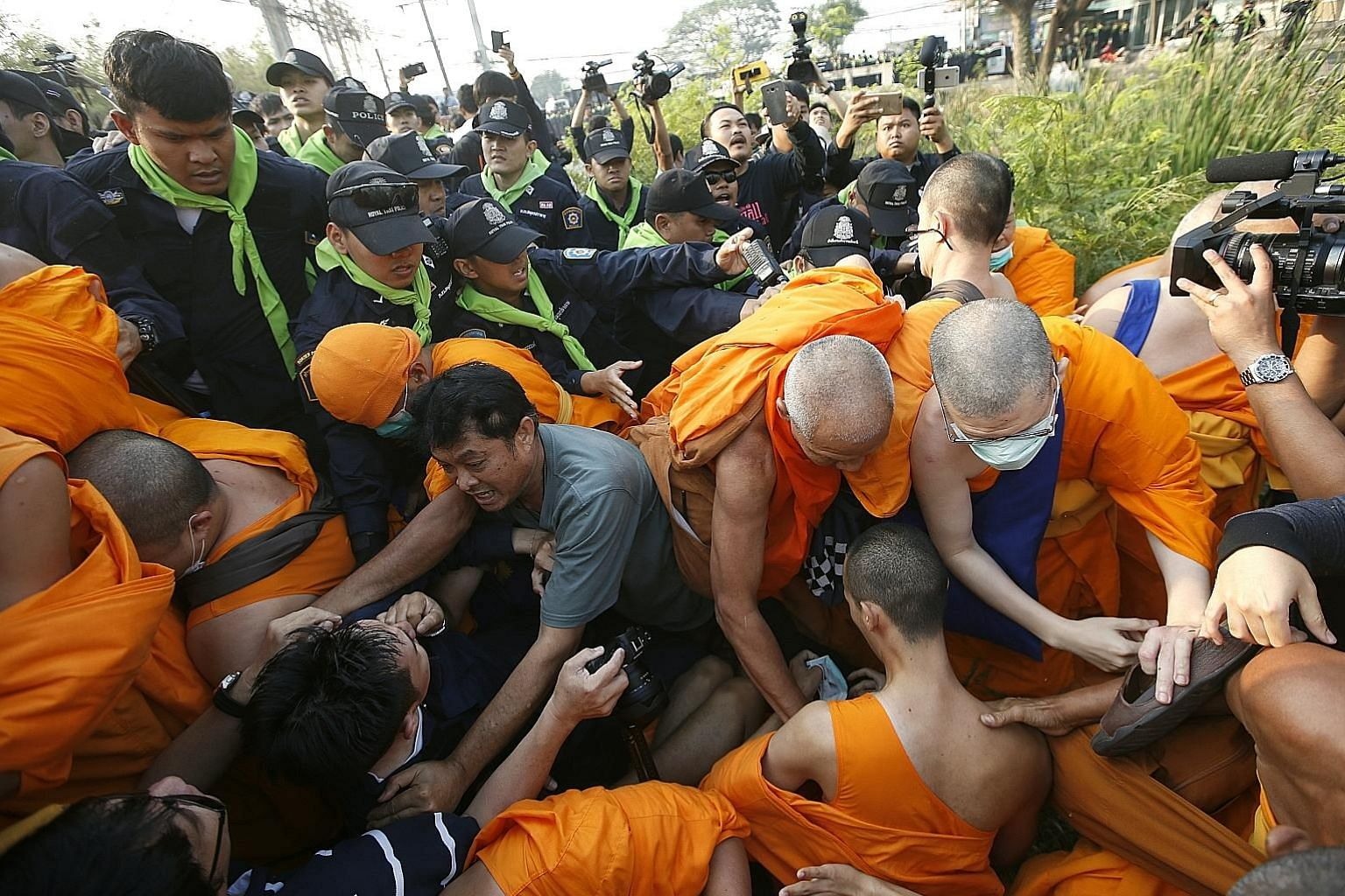Monks of Dhammakaya Temple and their supporters clashing with police outside the temple yesterday. Fugitive honorary abbot Phra Dhammachayo is believed to be holed up inside the compound.