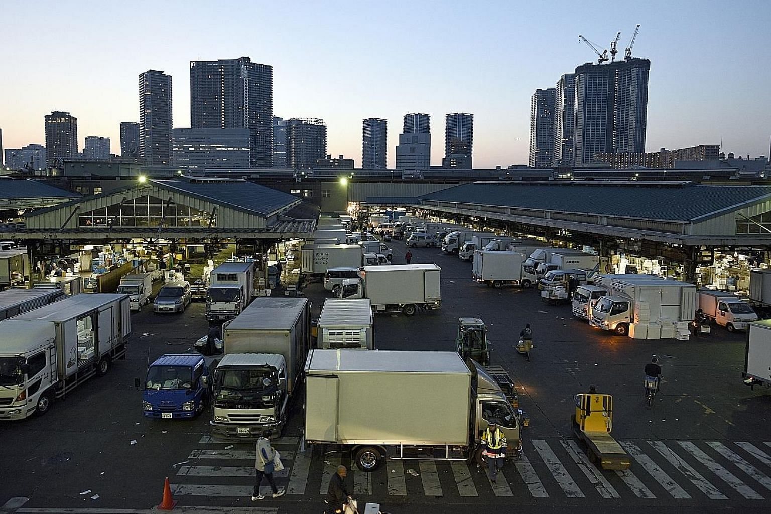 Above: High levels of toxic chemicals found in groundwater tests at the spanking-new Toyosu facility have frozen for now Tsukiji's move there. Right: Besides merchants and wholesalers, the fish auction at Tsukiji also draws crowds of tourists. Tsukij