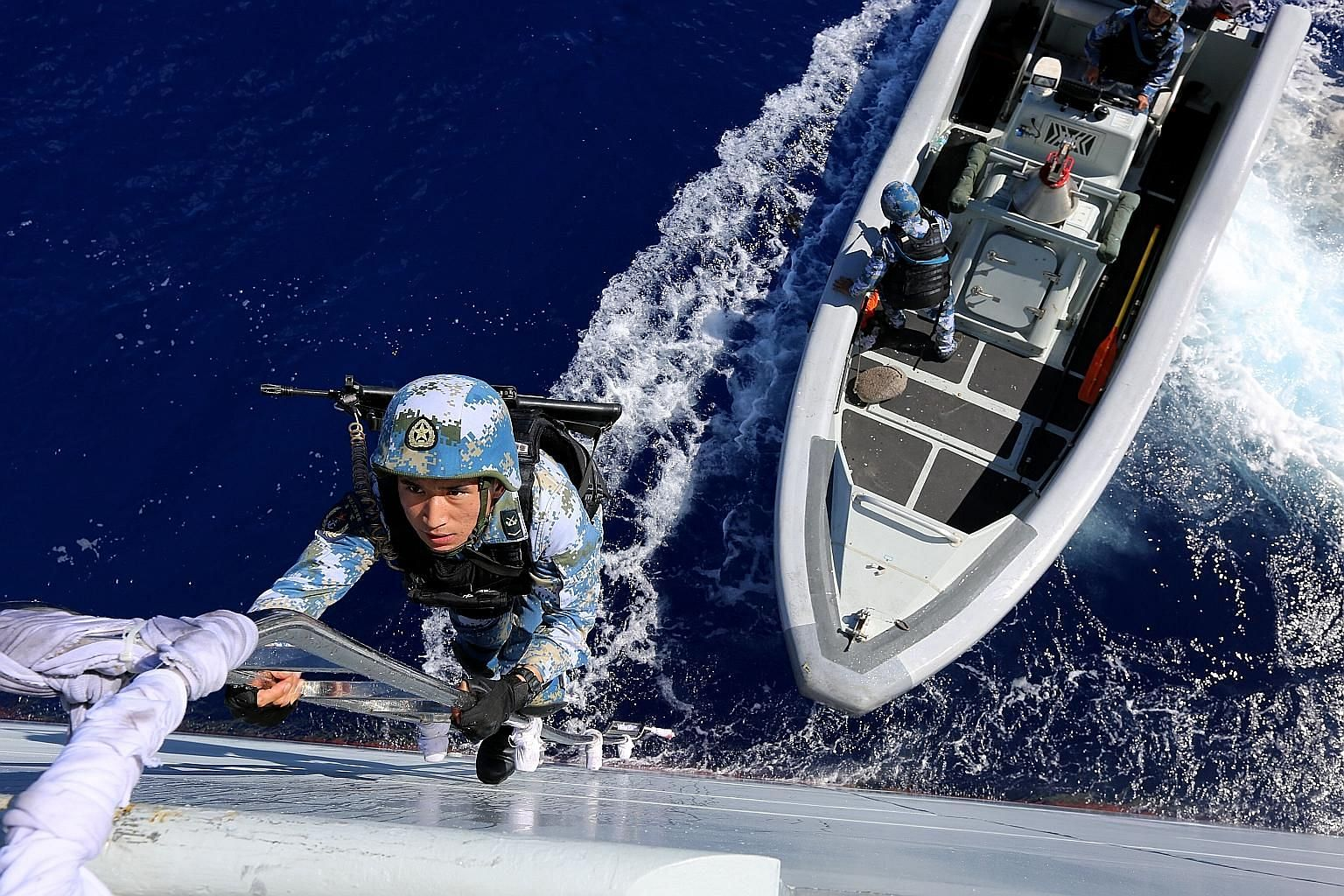 """Above: Special agents trying to land on the deck of a """"hijacked"""" ship in one of the simulated exercises conducted by China's South Sea Fleet in the eastern Indian Ocean. The flotilla of warships, consisting of guided-missile destroyers Haikou and Cha"""