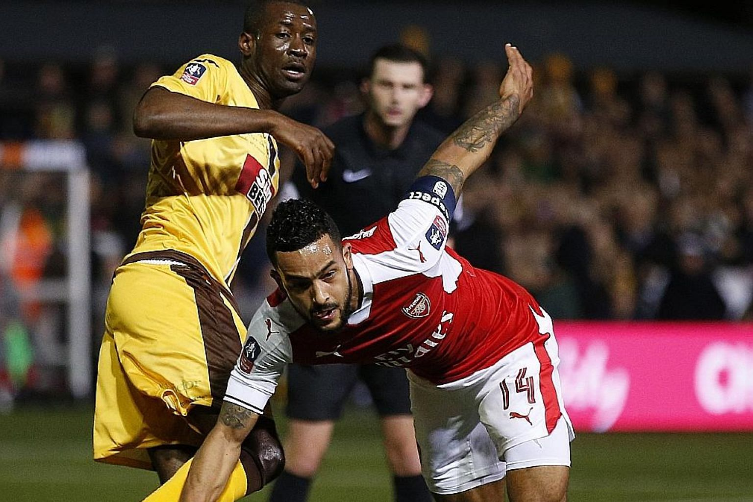 Arsenal forward Theo Walcott fighting with Sutton midfielder Bedsente Gomis for the ball. He scored his 100th goal for the Gunners when he netted in the 55th minute.