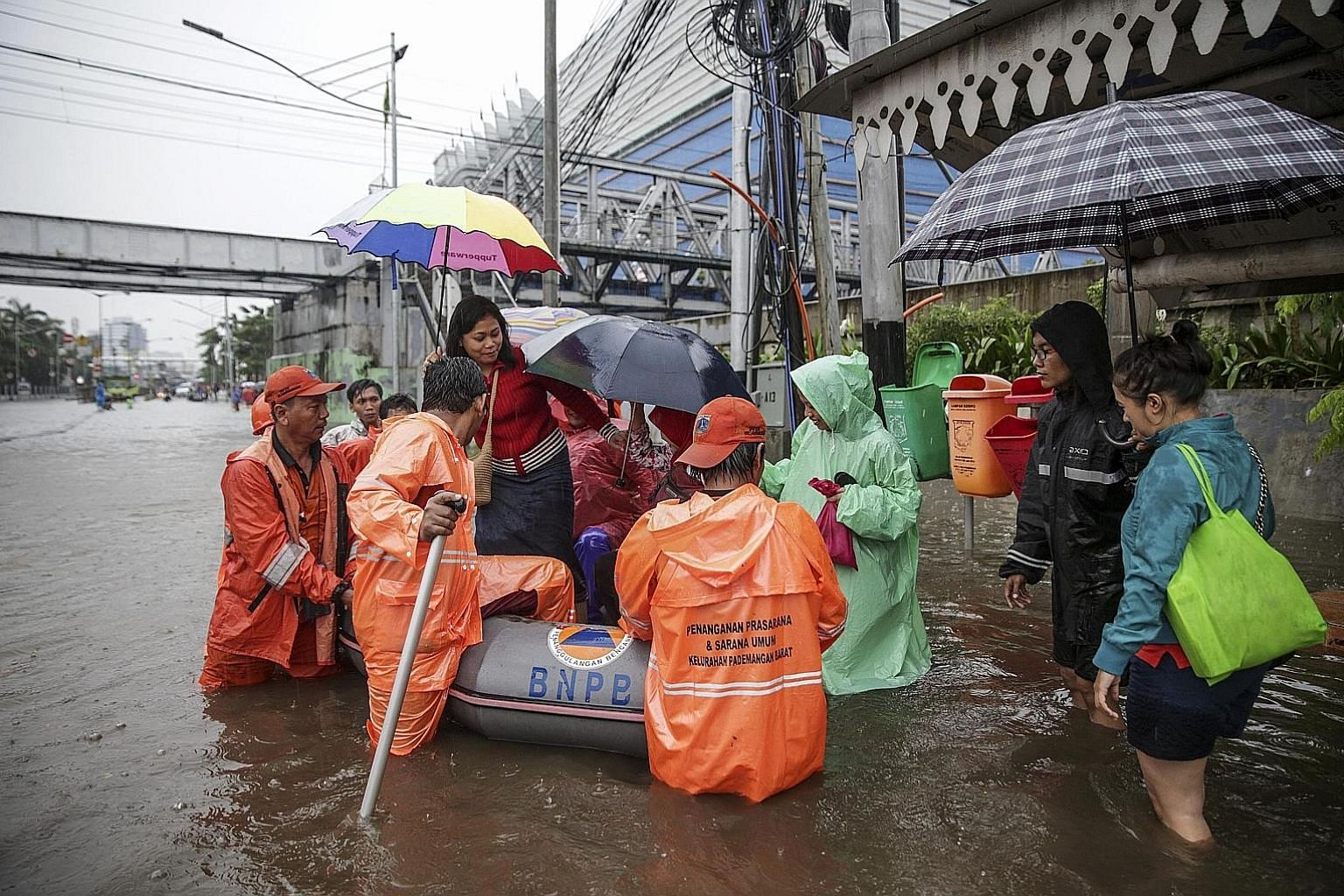 Above: Residents in a flood-hit neighbourhood of Jakarta being helped into a rubber boat yesterday. Left: Indonesian air force soldiers assisting stranded residents as torrential rain triggered widespread flooding.