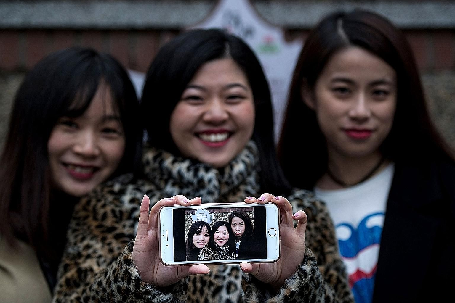 Ms Hu (far left) and her friends, Ms Wang Peng (centre) and Ms Peng Lin, with a selfie they took on Jan 8. Such virtual makeovers have propelled Meitu to the top ranks of downloads in China.