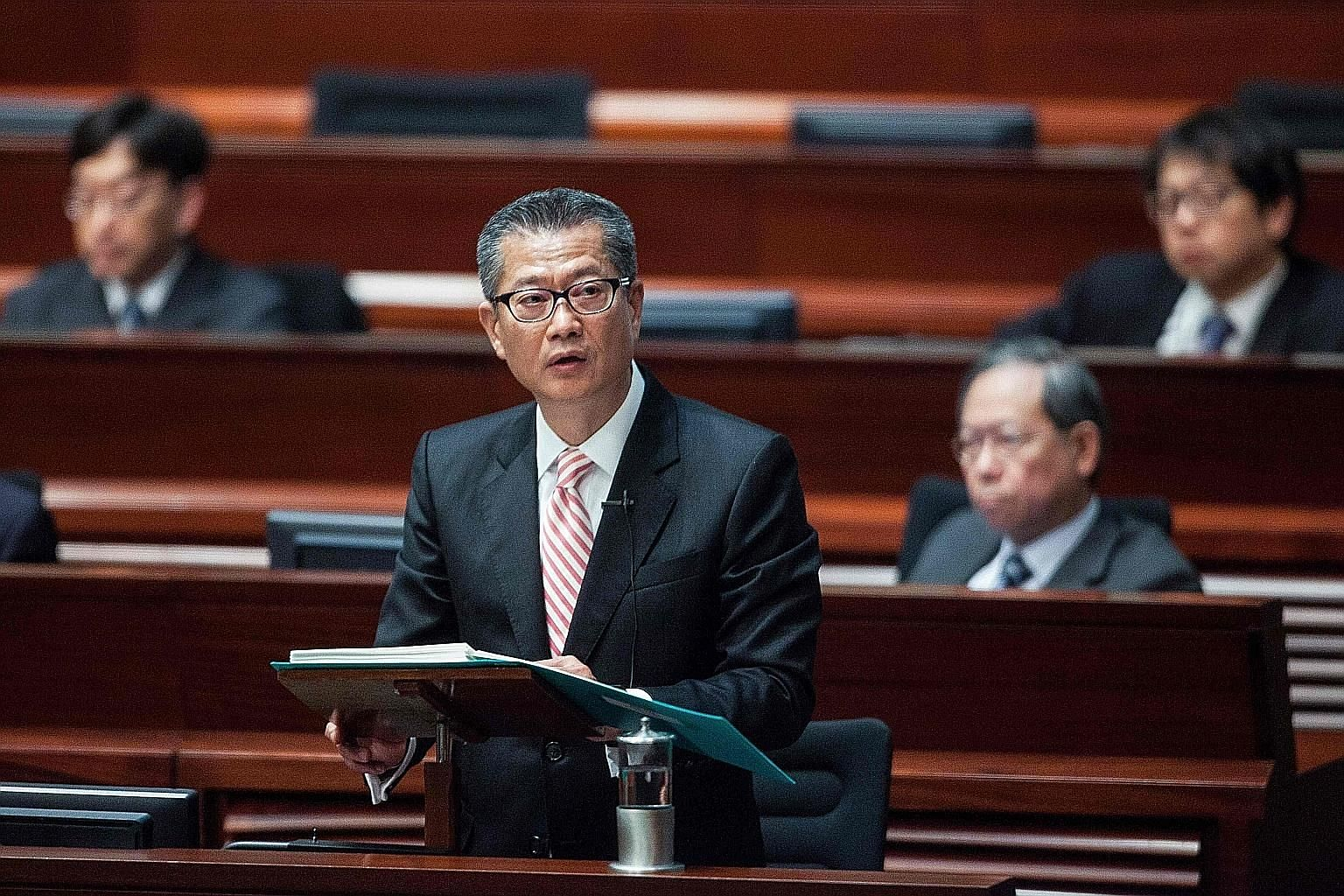 "Mr Chan delivering the 2017 Hong Kong budget speech at the Legislative Council yesterday. With a surplus of HK$92.8 billion (S$17 billion), the former development minister announced billions in tax cuts and poverty relief in a budget hailed as ""forwa"