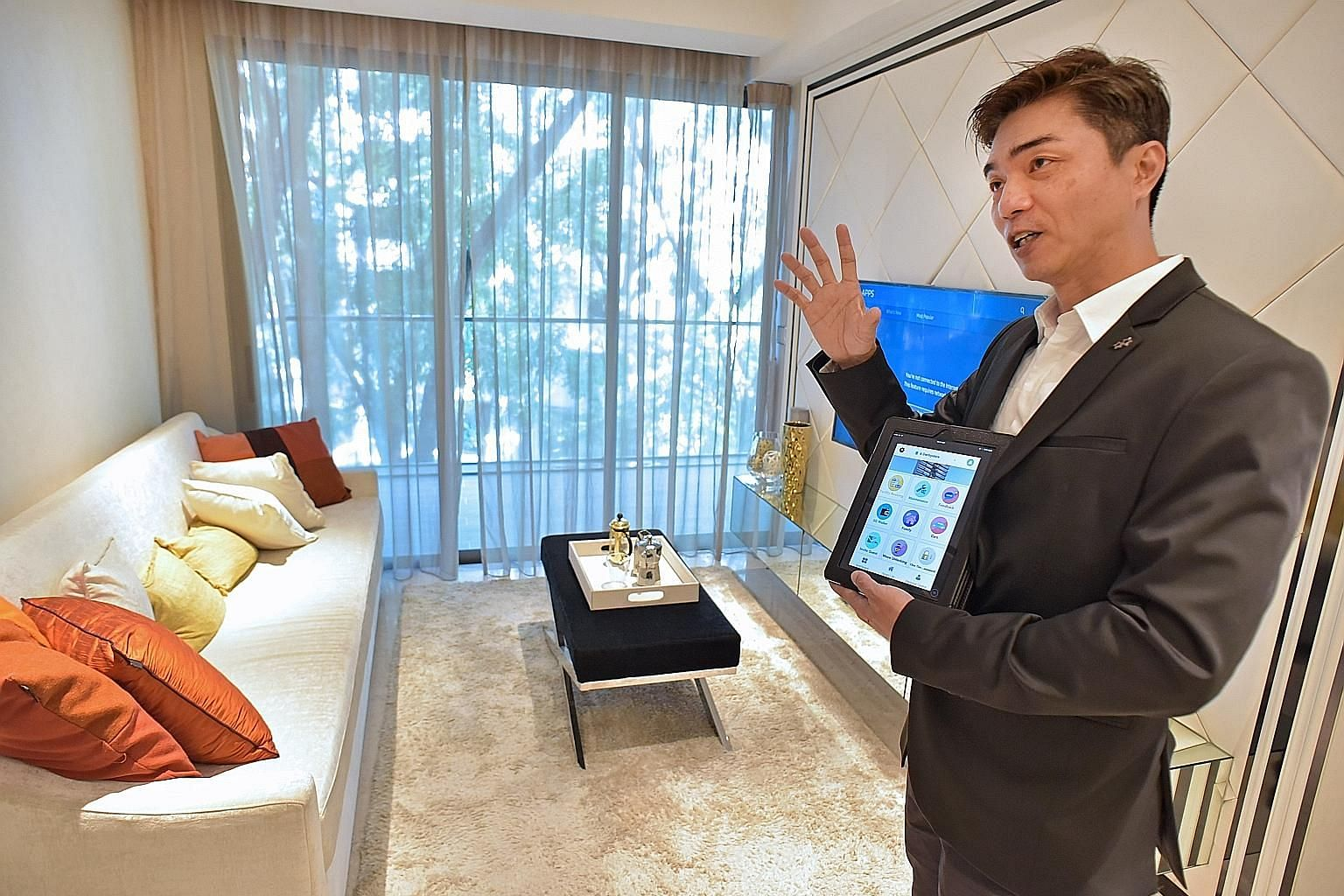 "Mr Andrew Tan using a tablet to explain the ""smart home"" concept at the showflat for Fantasia Investment's 6 Derbyshire. Qingjian has also unveiled its ""Internet-ready smart homes"" at the iNz Residence EC (right)."