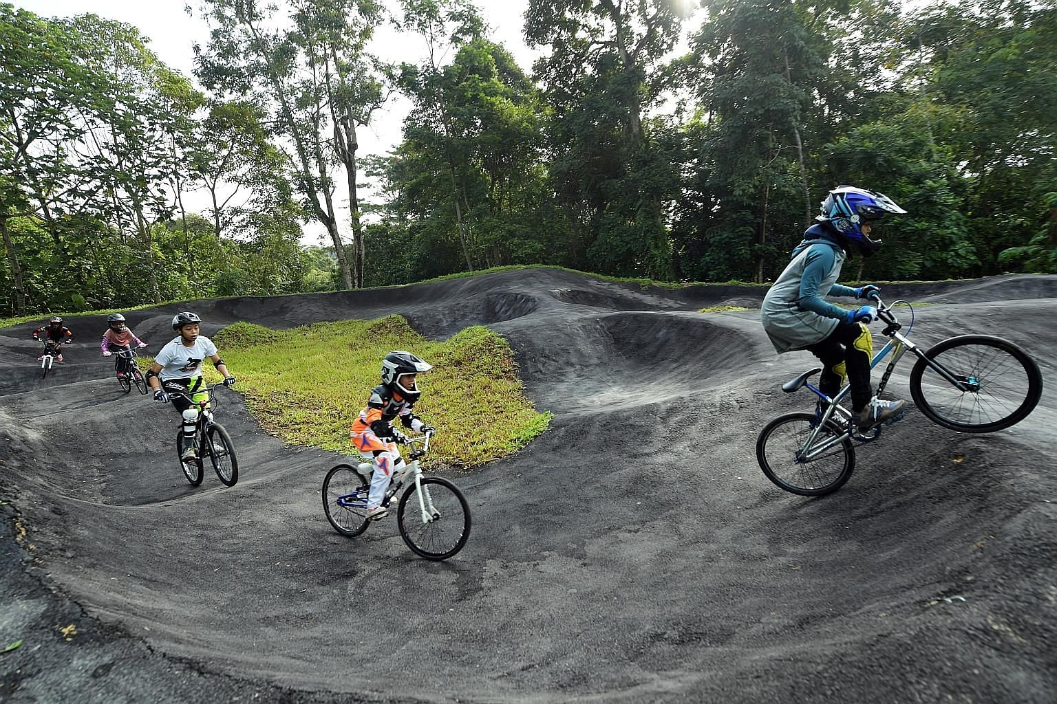 Children were among the biking enthusiasts who tried out Singapore's first pump track at Chestnut Nature Park yesterday. The track has four sections, called bowls, of varying difficulties. The park is now fully open after the northern section's openi