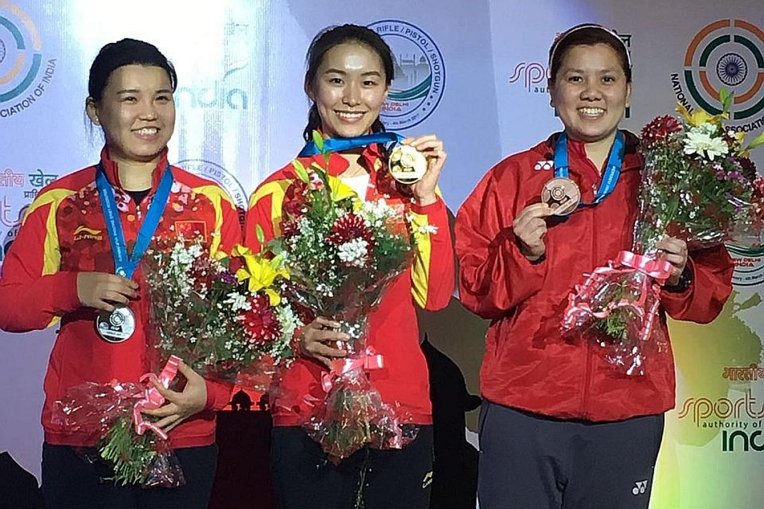 Singapore shooter Teo Shun Xie (right) celebrating bronze in the women's 10m air pistol at the ISSF World Cup. China's Lin Yuemei and Zhang Mengxue took gold and silver respectively.