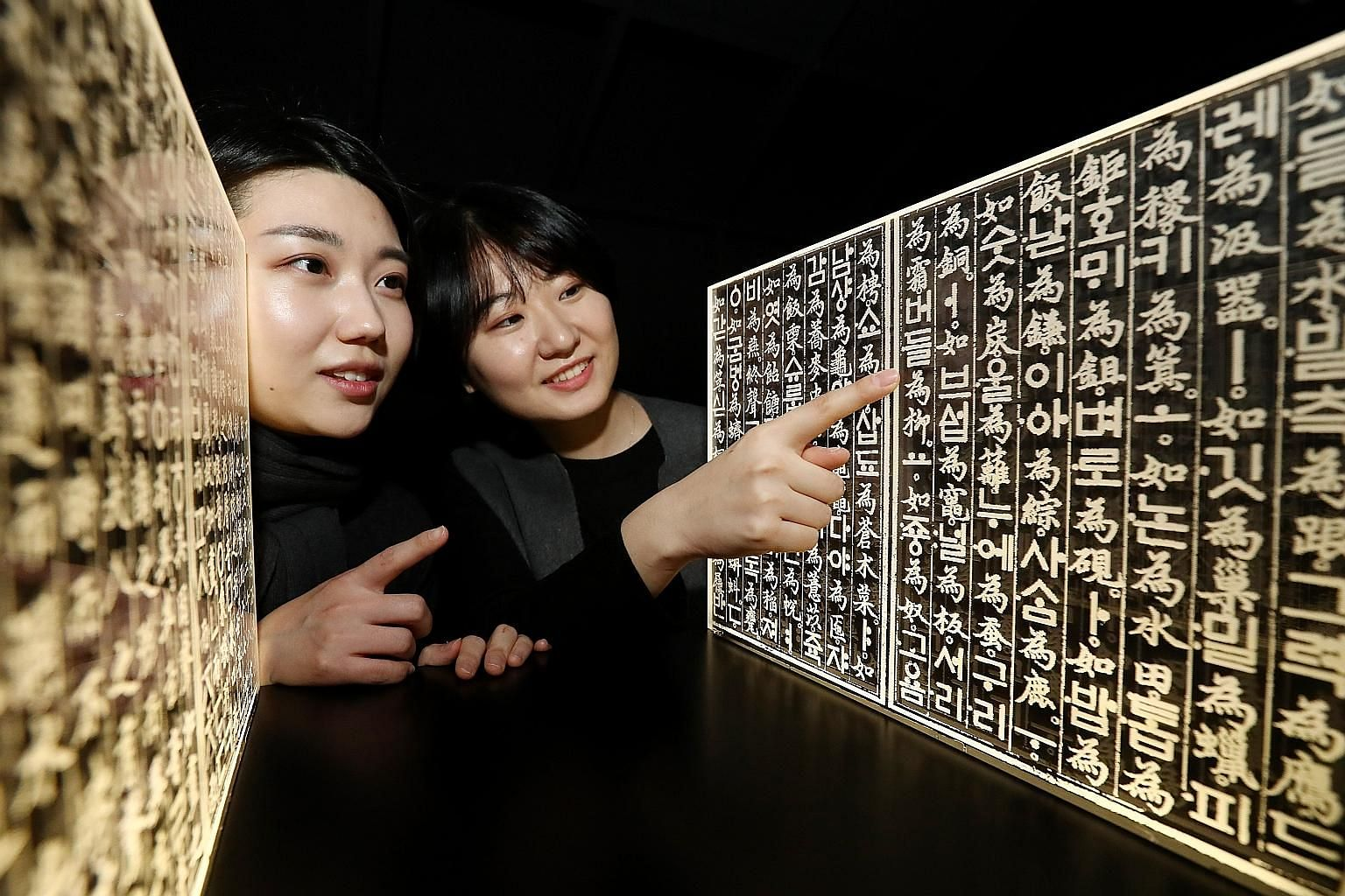Visitors looking at acrylic panels inscribed with characters from the book Hunminjeongeum at an exhibition yesterday at the National Hangeul Museum in Seoul. The event was organised to mark the 620th anniversary of the birth of King Sejong, who inven