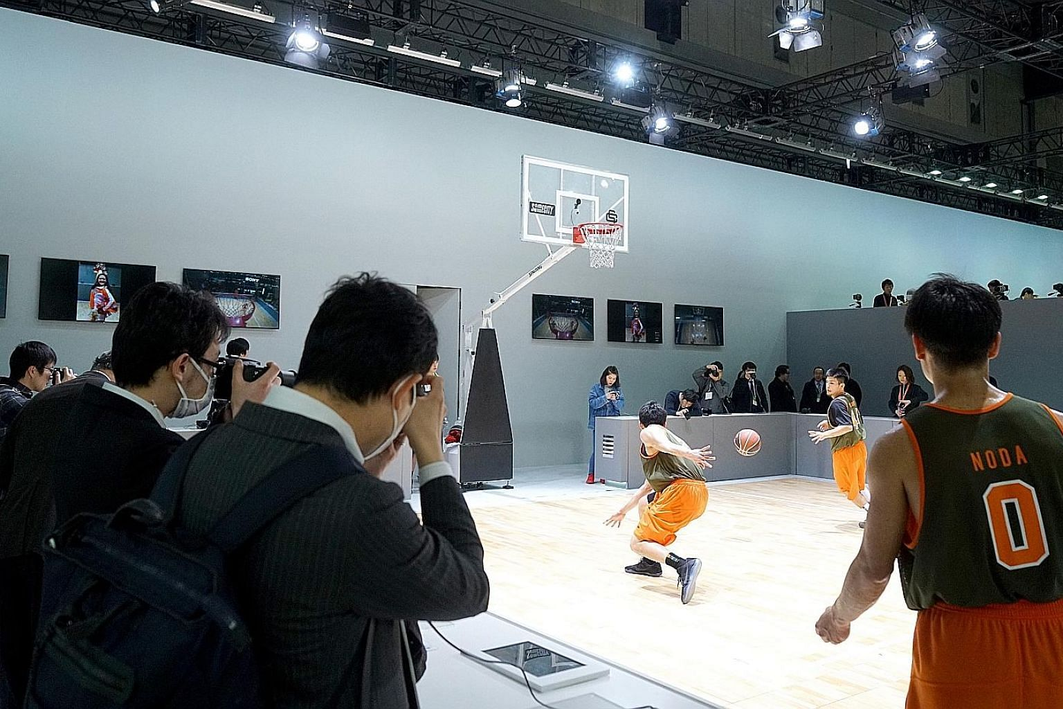 Visitors trying out cameras by taking photos of people playing basketball at the Sony booth of the CP+ Camera and Photo Imaging Show in Yokohama last week.