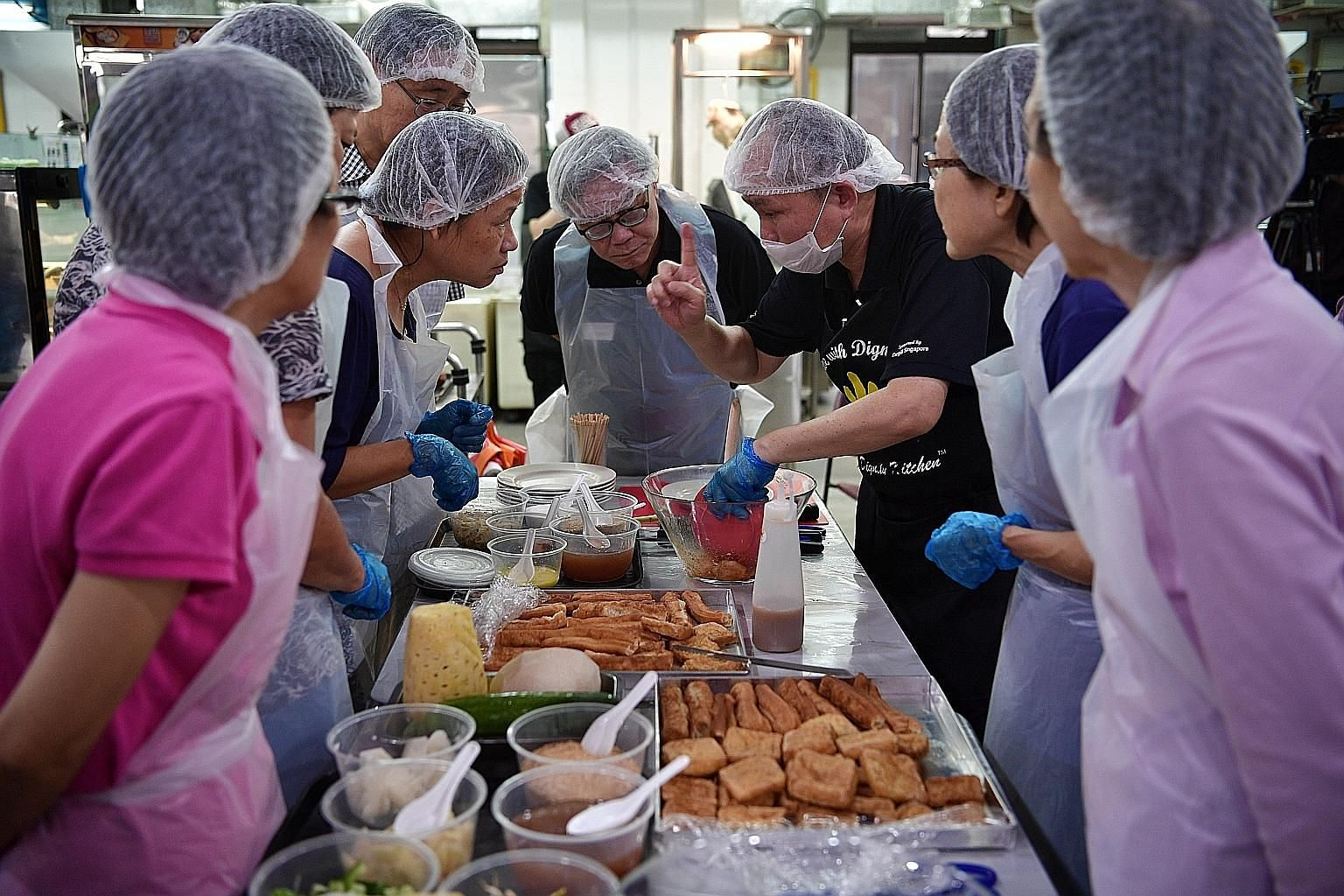 Participants learning how to make siew mai and rojak at a workshop held last year by Dignity Kitchen, a social enterprise that helps disadvantaged individuals train to become hawkers. The writer says the profile of the next generation of hawkers is c