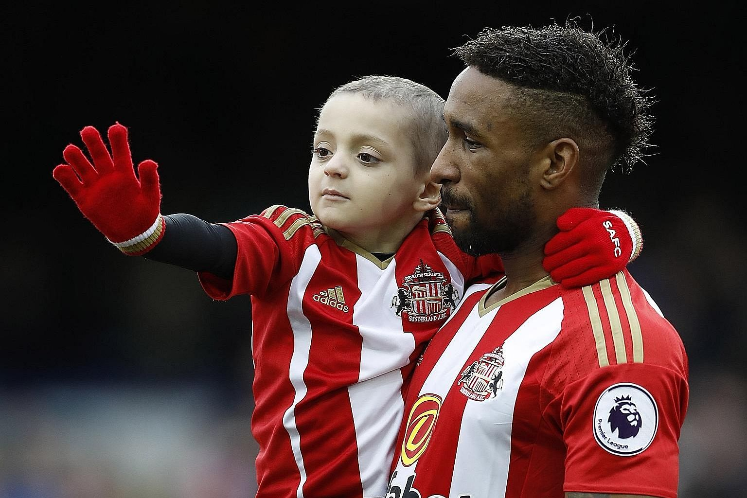 Sunderland's Jermain Defoe carrying out cancer-stricken fan Bradley Lowery before the match at Goodison Park. Everton and fans of all colours have contributed funds towards experimental treatment pioneered in the US which may cure or kill the five-ye