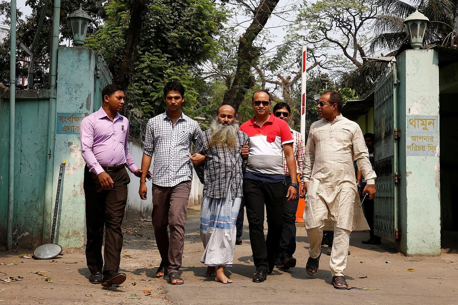 Security personnel with Maolana Abul Kashem, spiritual leader of the banned Jamayetul Mujahideen Bangladesh group, yesterday. Police say Kashem had met the alleged mastermind of the Dhaka cafe attack, Tamim Chowdhury, several times.