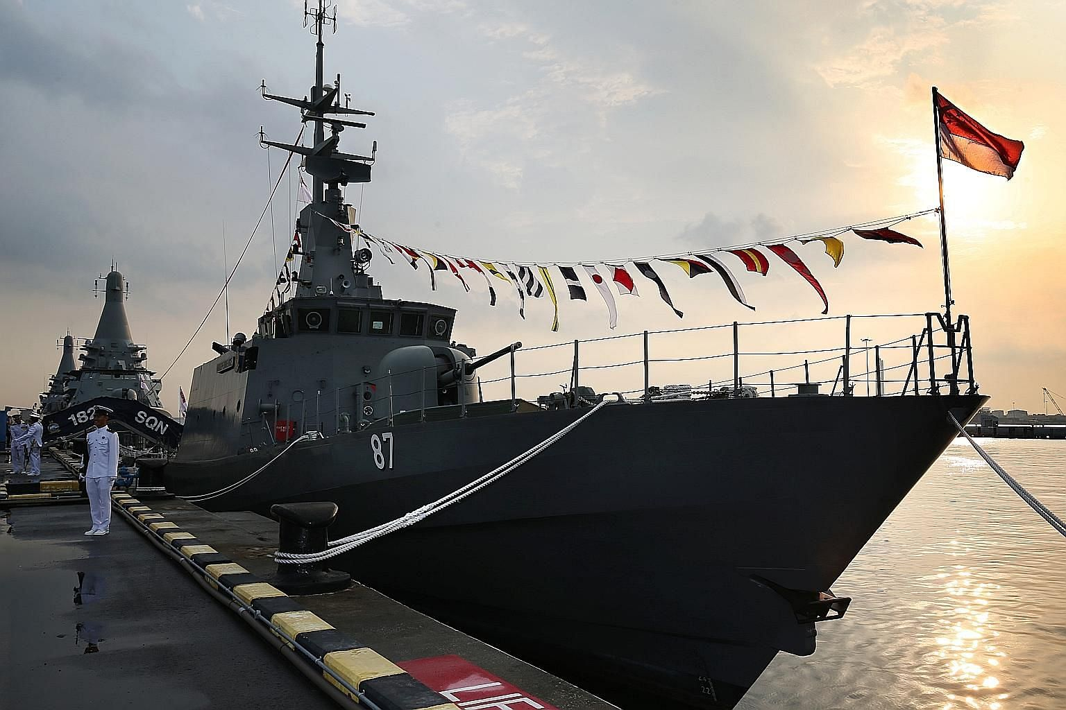 Top: RSS Independence (in front) and LMV Independence (background) at the decommissioning ceremony at Tuas Naval Base yesterday. Above: Singapore Navy sailors bade farewell to the patrol vessel during the ceremony, as flags on the warship were lowere