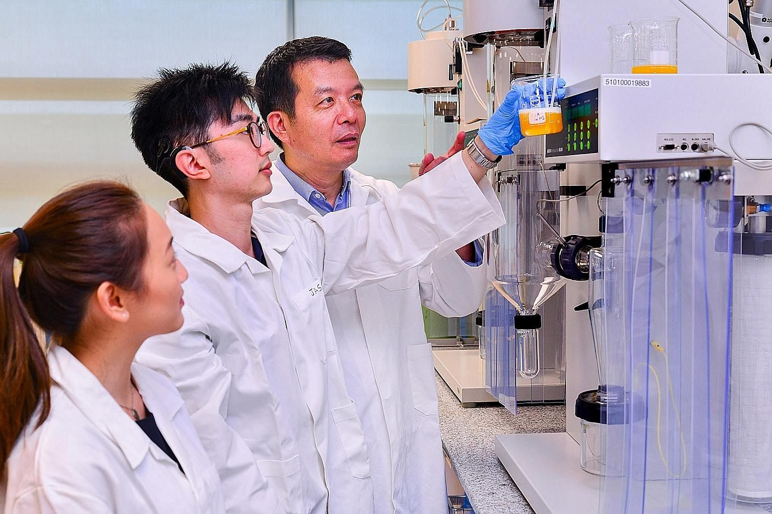 NTU's Food Science and Technology programme director William Chen, researcher Jason Quek and student Verene Chou doing an experiment on fruit juice.