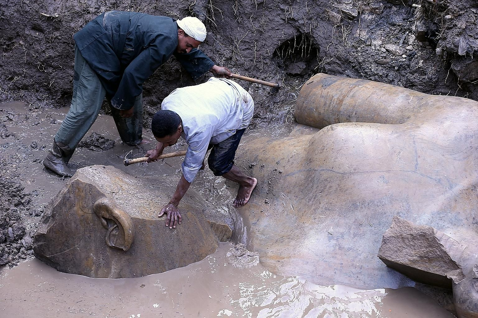 Workers preparing to lift parts of a statue for restoration after it was unearthed at Souq al-Khamis district in Cairo, Egypt, last Thursday. According to the Ministry of Antiquities, a German-Egyptian archaeological mission found two 19th dynasty ro