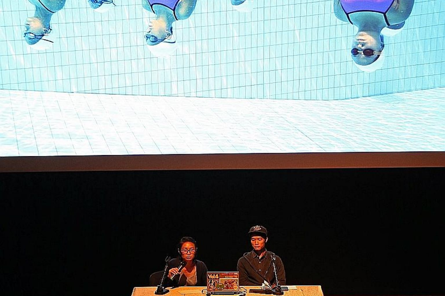 Straits Times photojournalist Caroline Chia, accompanied by colleague Mark Cheong, at yesterday's session at National Museum of Singapore, talking about a photo of a synchronised swimming team she had taken.