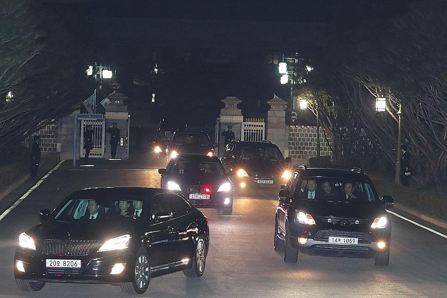 South Korea's impeached president Park Geun Hye (in car at left) being driven away from the presidential Blue House as she returned to her private residence in Seoul on Sunday, two days after the Constitutional Court's verdict confirming her removal