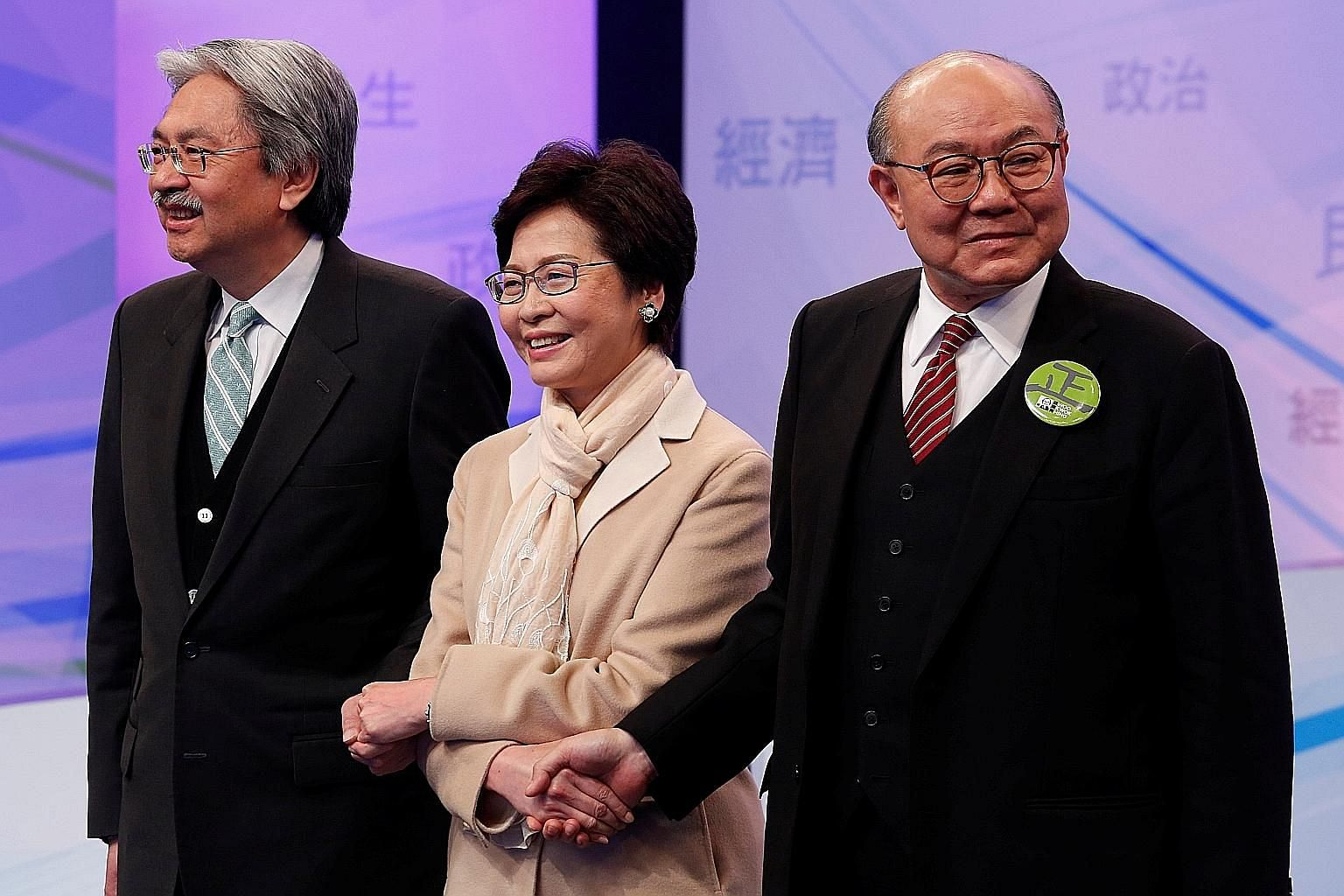 Chief executive candidates John Tsang (left), Carrie Lam and Woo Kwok Hing sharing the same stage for the first time last night to spar on political, economic and livelihood issues, with the hope of winning over public opinion.