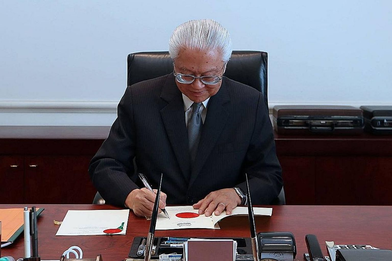 "President Tan, seen here signing off on the Budget, said in a Facebook post yesterday that the discretionary power the elected president wields in the Budget process is ""a constitutional safeguard""."