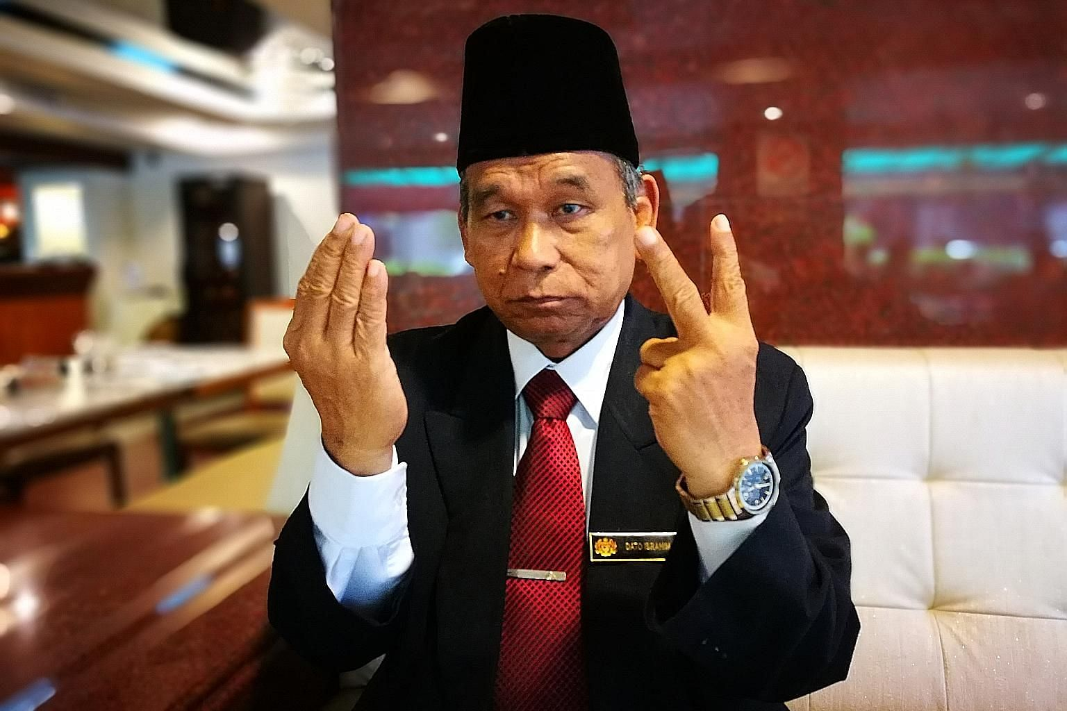 Self-styled Raja Bomoh Ibrahim Mat Zin shows how he prays for Malaysia's protection against North Korea, holding up two fingers to bless both nations.