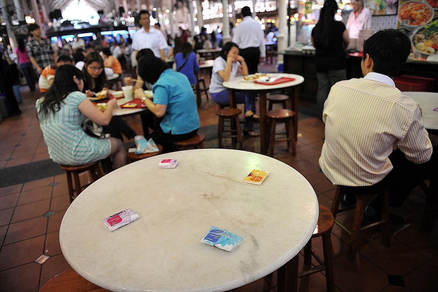Packets of tissue paper being used to reserve a table at a hawker centre. Mr Ronald Lee says such a practice should be disallowed.