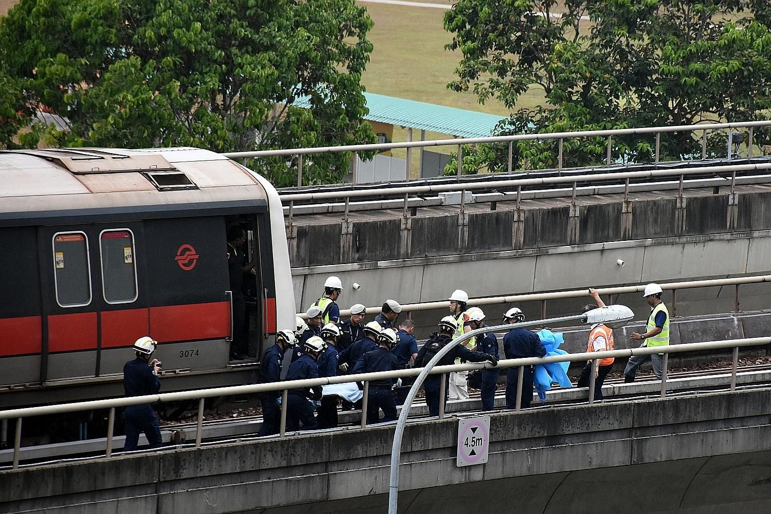 Paramedics from the Singapore Civil Defence Force retrieving the body of one of the two SMRT maintenance staff who were killed in the accident along the train track near Pasir Ris MRT station on March 22 last year.