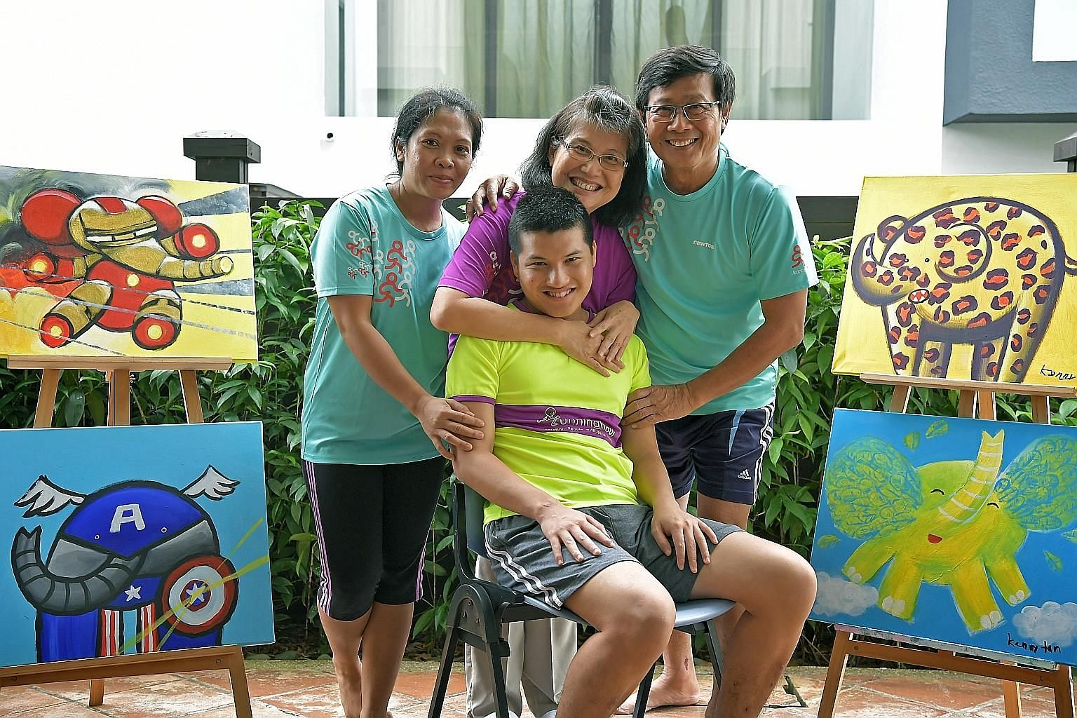Mr Kenny Tan, 24, with his parents - housewife Selina Tan, 63, and retiree Vincent Tan, 64 - and their helper Nova Baniaga, 36. Mr Tan's family will be selling prints of his artwork, with half of the proceeds going to Runninghour. Last year, Mr Tan's